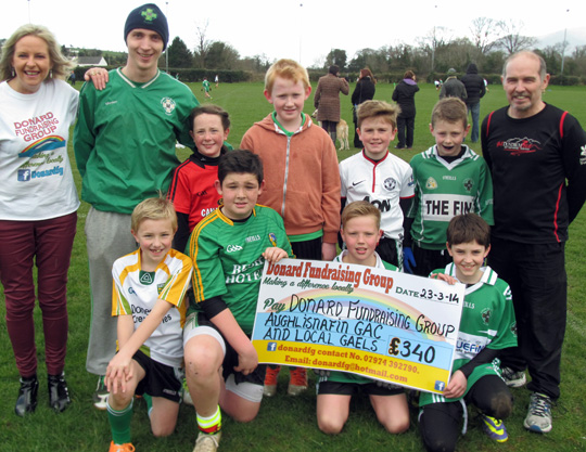 Donard Fundraising Group PR/Publicity Officer Jacqui Mason, Aughlisnafin Senior Team player and U12's Manager Francis Boden alongside some of the U12 players with the Donard Fundraising Group's Chairman Paul Madden.