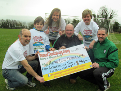 Donard Fundraising Chairman Paul Madden and his son Raphael with volunteers Jacqui Mason and Kate Pell accept a cheque for £940 from Catlewellan Town FC representatives Ben Corrigan and Conor Stratton.  The Club raised the money from a recent 'Night at the Races' and through 'Movember' sponsorship when club and team members grew beards and moustaches.