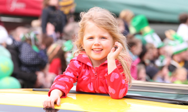 The best seat in the house. A young participant in the parade enjoyed her view from teh sun roof of a  a big yellow American cadillac