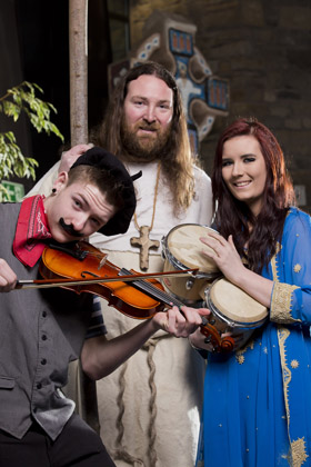 St Patrick aka Martin Burns celebrate the theme of world music of dance for St Patrick's Celebrations in Downpatrick with local students from the South Eastern Regional College Graham Walker and Chelsea Rogan.