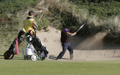 A doctor from the ER hospital in New York plays a sand shot at Royal County Down.
