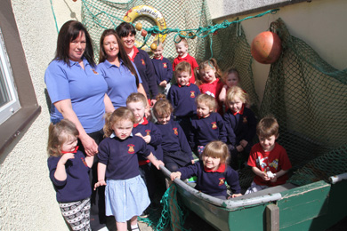 Tiny Toons assistants Karen Fitzsimons and Jennifer Davey with Leader Muala Mulholland, and some of the children al aboard a boat in their outdoor palyground.