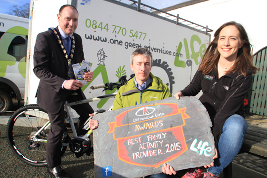 Newry Mourne and Down District Council, Councillor Mickey Ruane, tries out an e-bike after congratulating the Life Adventure Centre on its prestigious win. Pictured are Centre director Martin McMullan and Sarah Nelson, Marketing Officer with OutdoorsNI.com