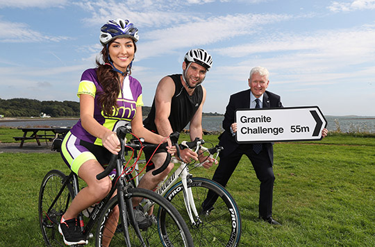 THERAPIE MISS NI GEARS UP FOR THE ULTIMATE GRANITE CHALLENGE:   Pictured putting the wheels in motion are Therapie Miss Northern Ireland, Emma Carswell, with Rowan Quinn and Chief Executive of AMH, David Babington.